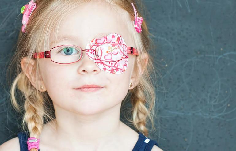 ребенок в очках с закрытым глазом