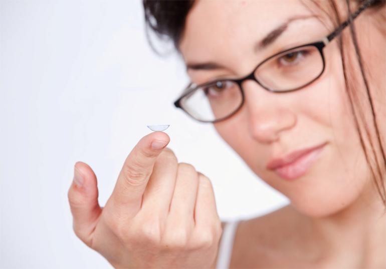 женщина в очках держит линзу